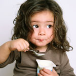 toddler girl eating yogurt with a spoon to her mouth.