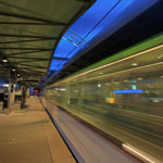 a photo of a train station platform with a blurred train going by.